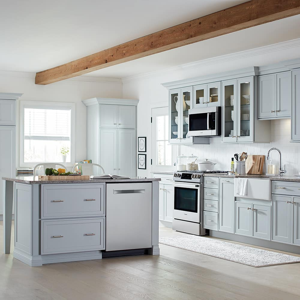 A stainless steel dishwasher with a hidden panel in a spacious kitchen