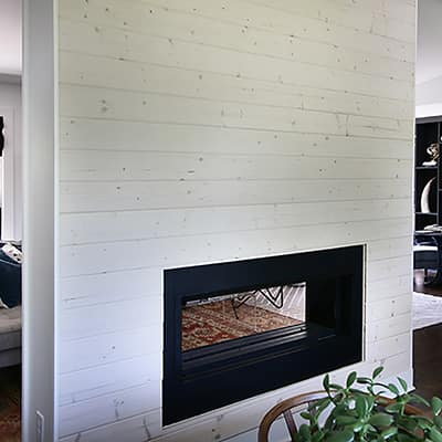 A modern shiplap fireplace with beachwood boards.