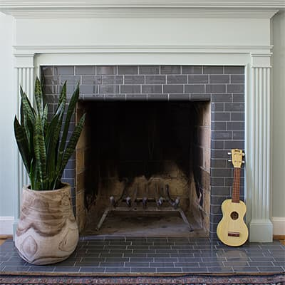 A DIY tile fireplace makeover with gray peel and stick tile.