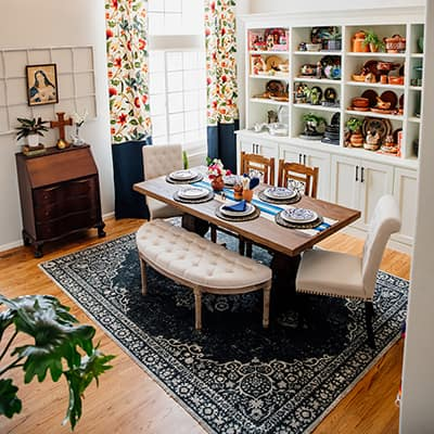 A dining room with white built-in bookshelves.