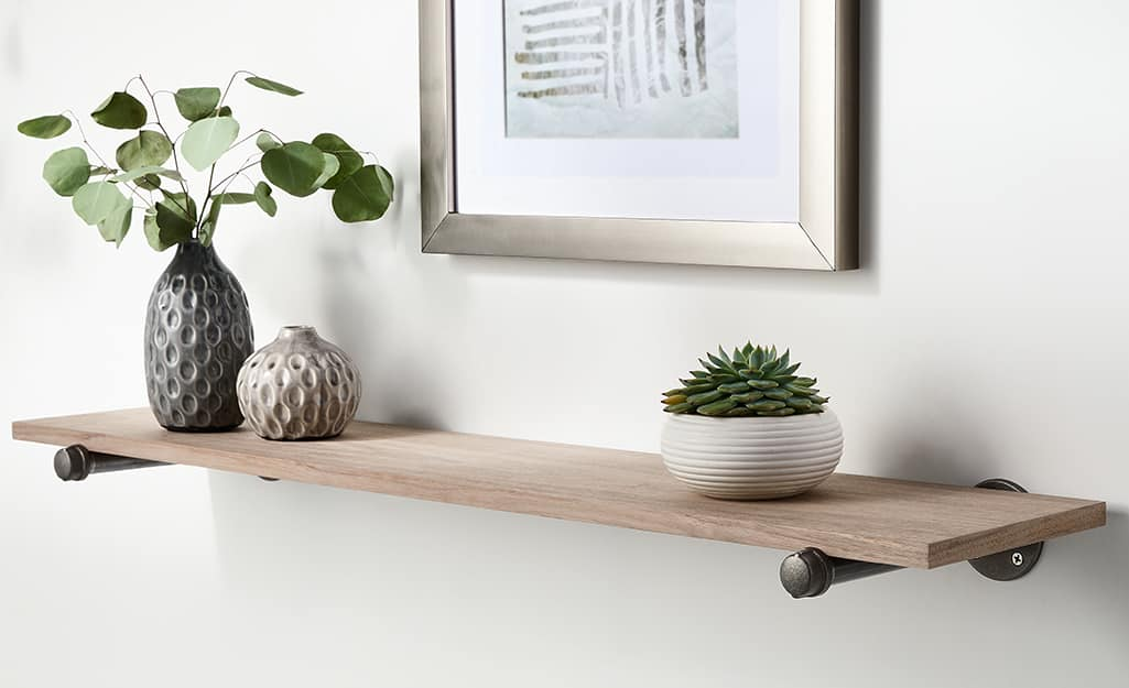A shelf and photo attached to a wall with wall anchors.