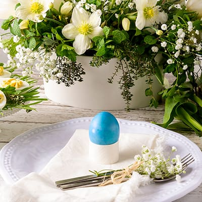 A blue Easter egg on a white plate with flowers in the background.