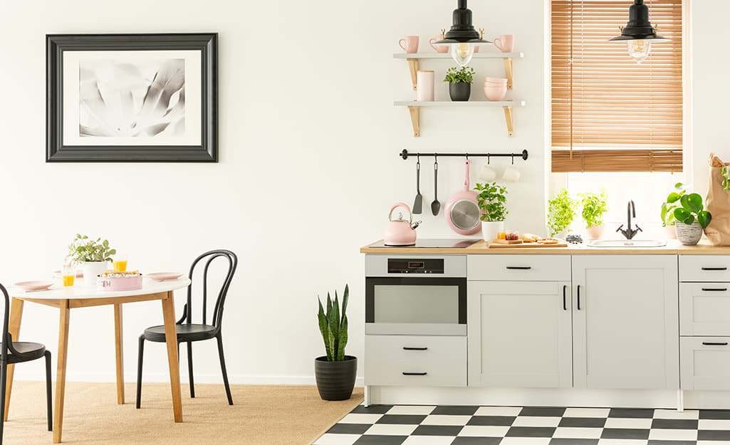 Checkerboard flooring plus black and white artwork in a simple kitchen.
