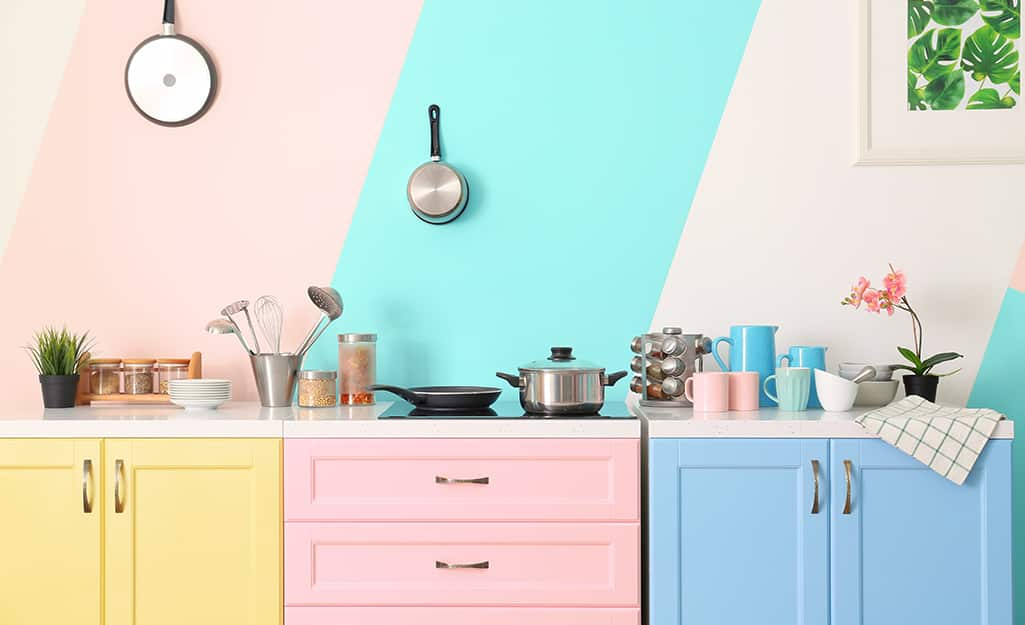 Colorful kitchen cabinets in yellow, pink and blue against a wall with an blue stripe.