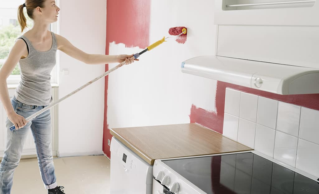 Woman painting an accent wall in a kitchen.