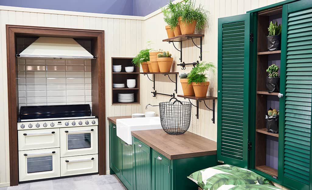 Planters with different herbs placed on hanging shelves in a white and green kitchen.