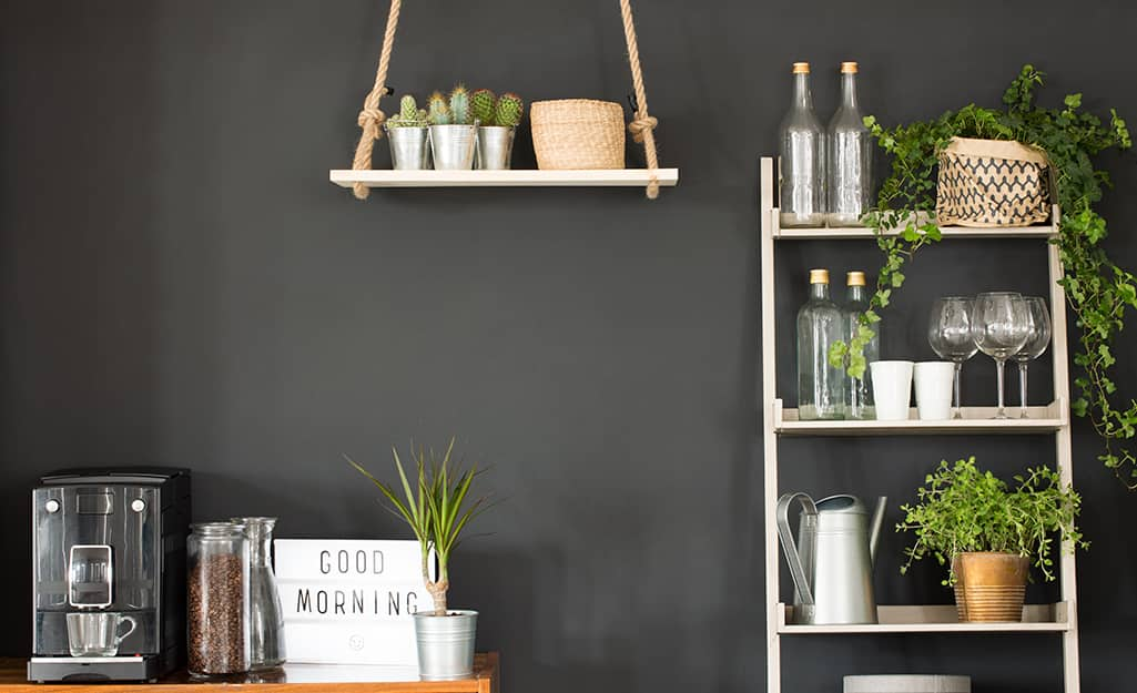 Hanging shelf and shelving against a black kitchen wall.