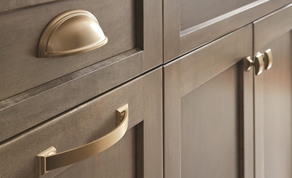 Brushed silver hardware set on a gray kitchen cabinet.