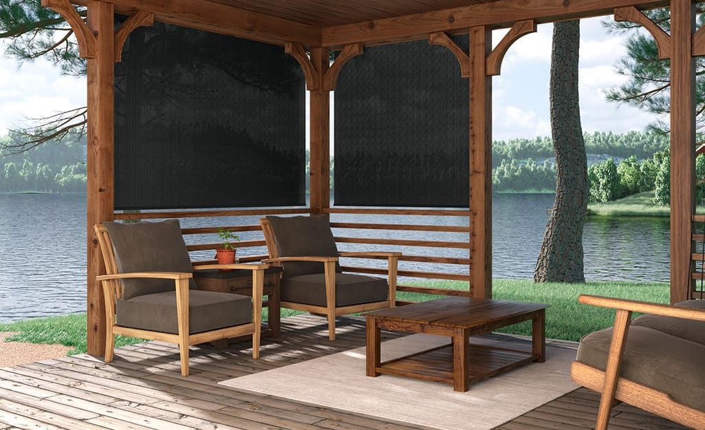 A porch off the lake with a pergola and exterior shades.