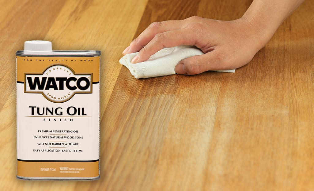 Someone rubbing a wood surface with a cloth and tung oil.