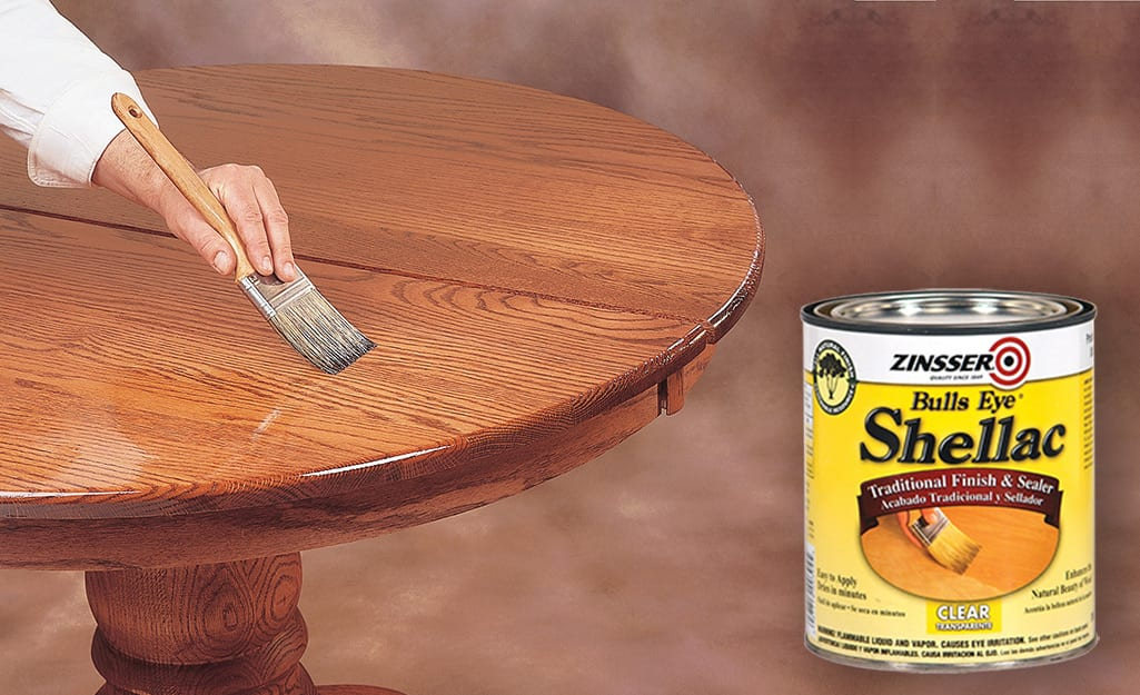 A can of Shellac showing a photo of it being brushed on wood.
