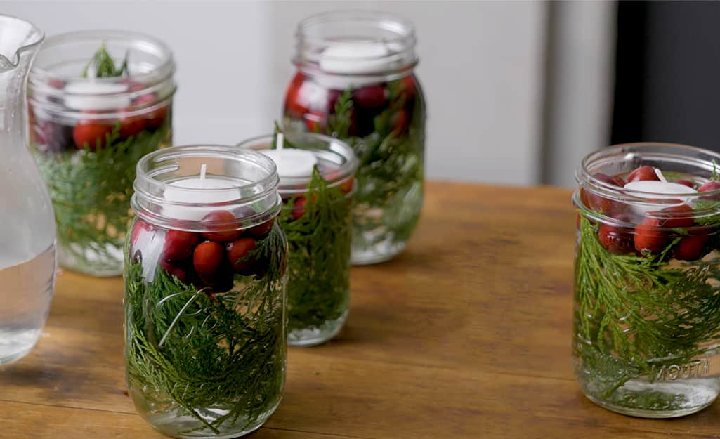 DIY candle holders made with mason jars filled with water, cranberries and floating candles