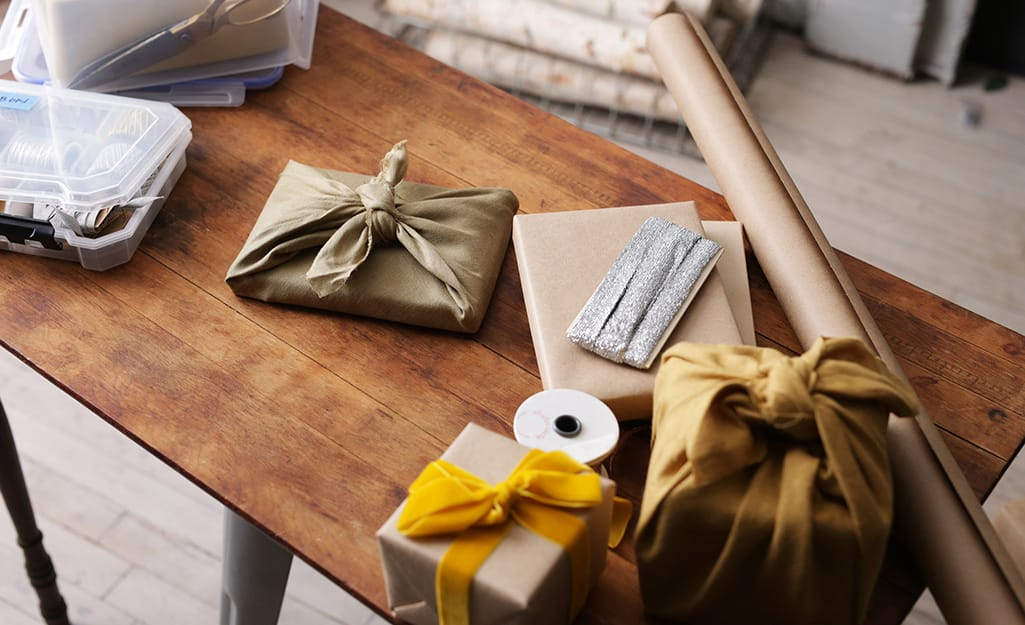 Gifts wrapped in linen,  a roll of craft paper and other holiday supplies