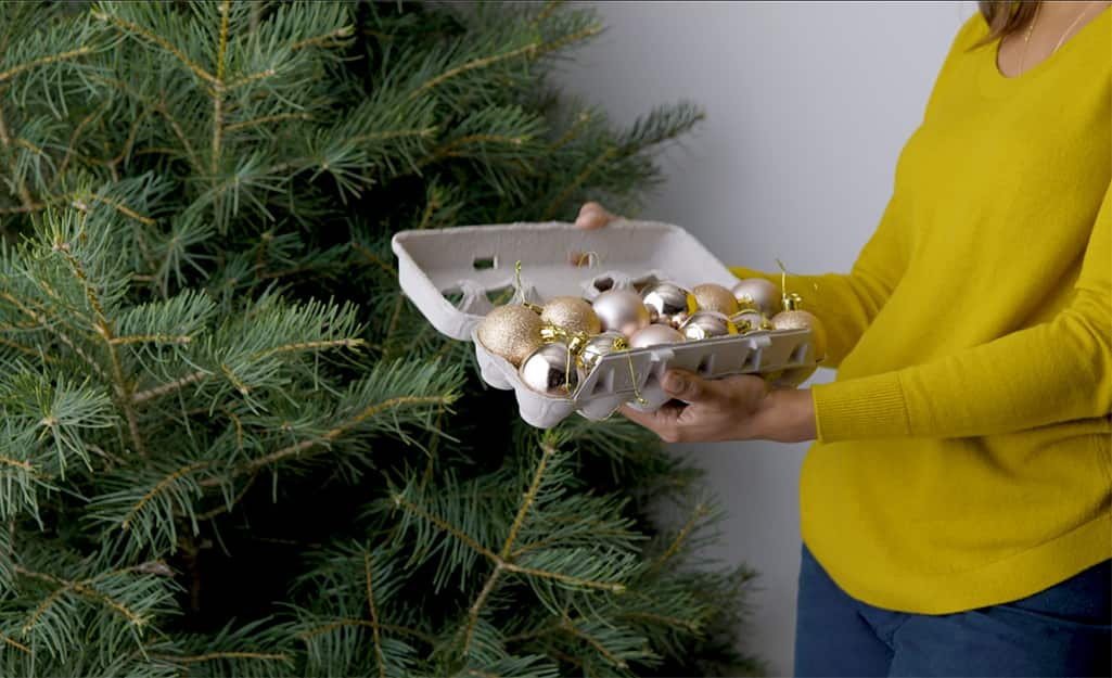 Woman placing holiday ornaments in used egg carton for storage