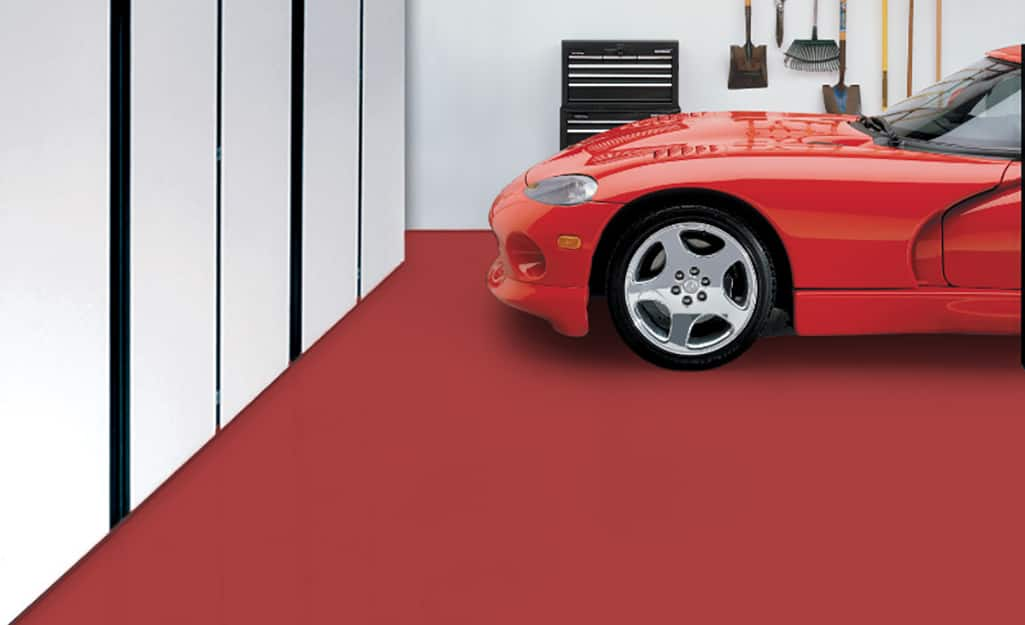 A car parks on a garage floor painted red.