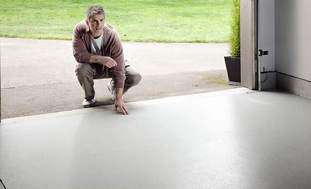 A person crouches just outside a garage coated with gray epoxy paint.