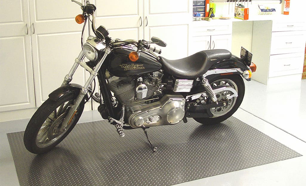 A motorcycle is parked on a flooring mat in a garage.