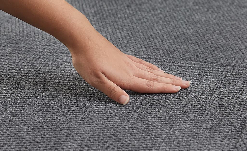 A person touches a gray indoor/outdoor carpet suitable for a garage.
