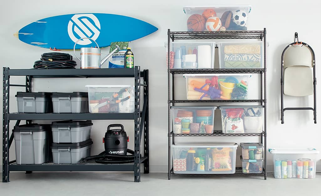 Clear plastic bins store toys and other belongings on garage shelves.