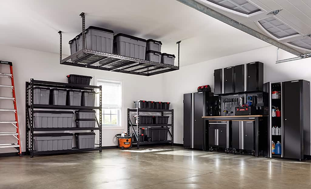 An overhead storage rack holds containers in a garage.