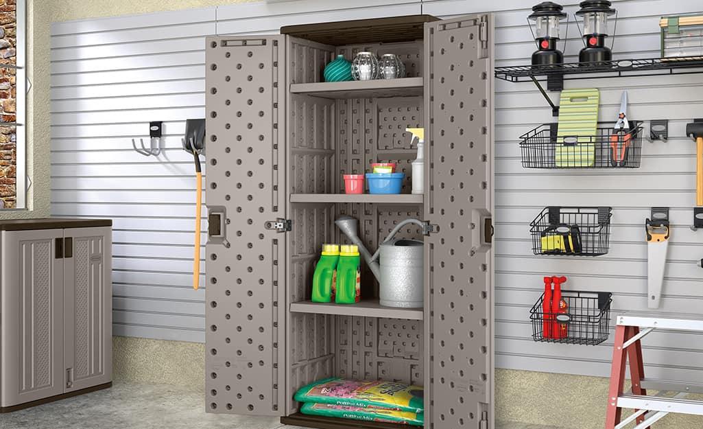 A storage cabinet against a garage wall holds gardening supplies.