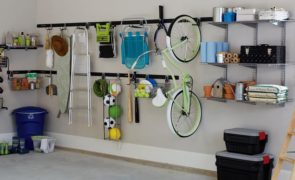 Track systems on a garage wall provides vertical storage for a bicycle, step ladder, sports equipment and more.