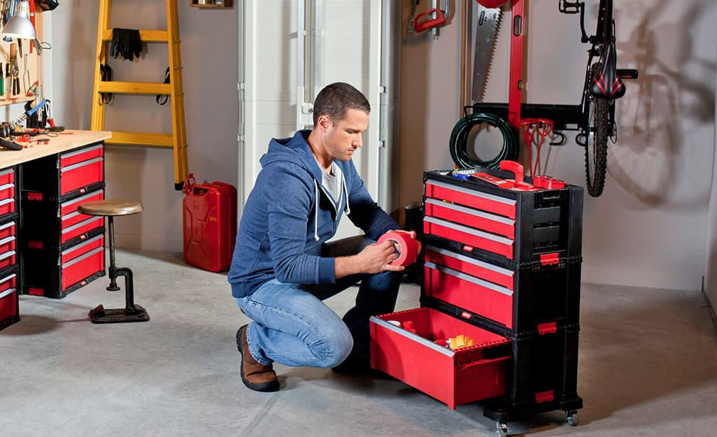 A person removes supplies from a garage tool chest.