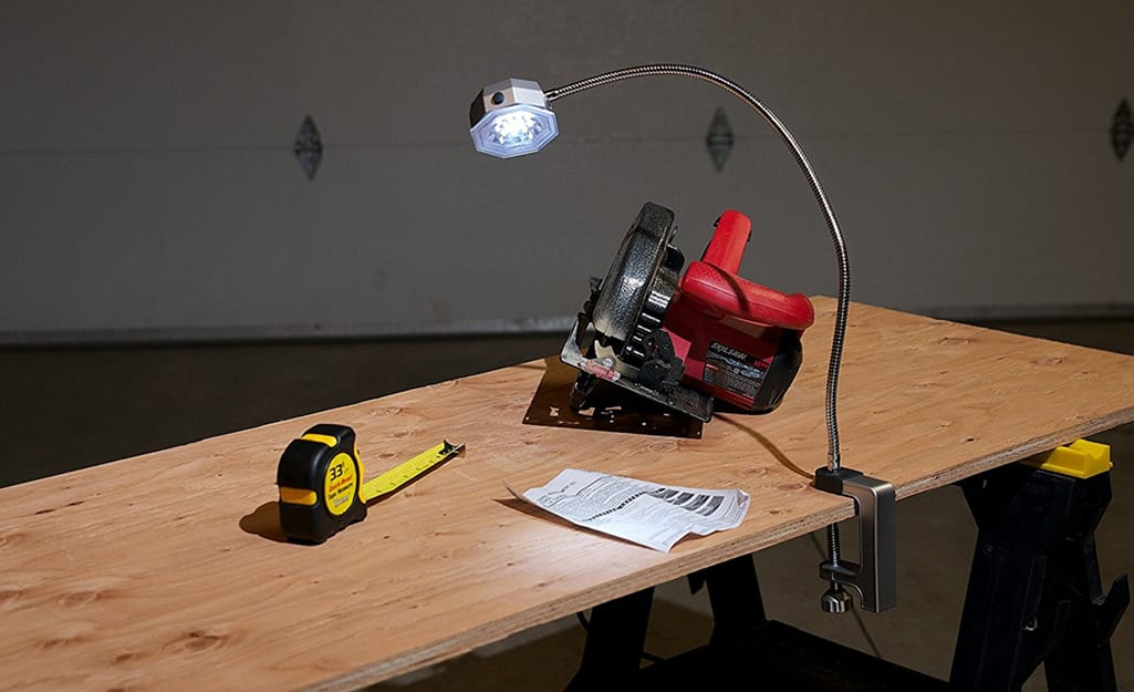 A workbench provides a surface for a tape measure and a circular saw.