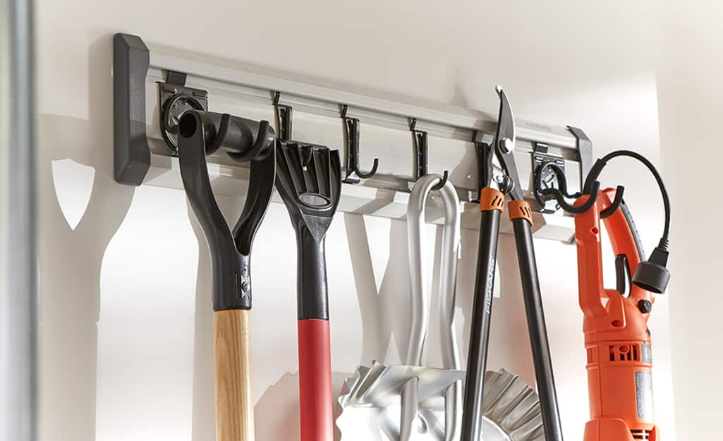 Wall hooks support large tools for yard work.