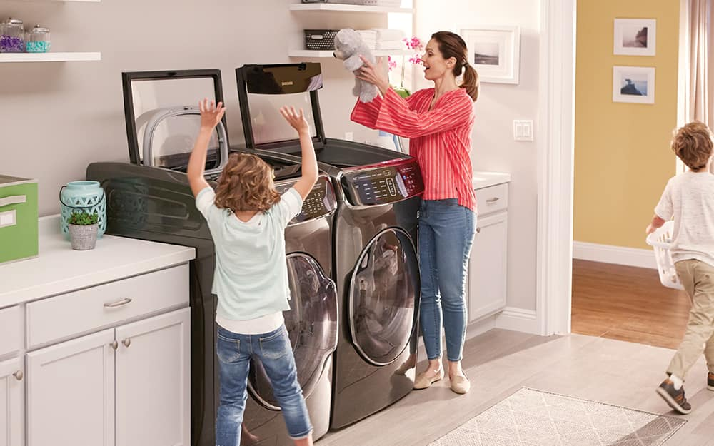 A child helps his mother add clothes to a washer and dryer in a laundry room.