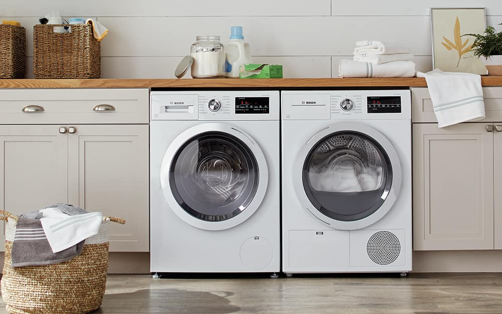A white washer and matching dryer sit next to each other in a laundry room.