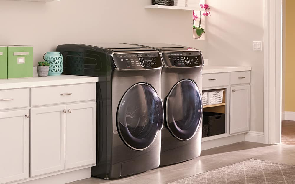 A black front-load washer and gas dryer sit side-by-side in a laundry room.
