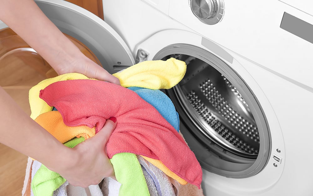 A person holds a handful of colorful laundry in front of a dryer.