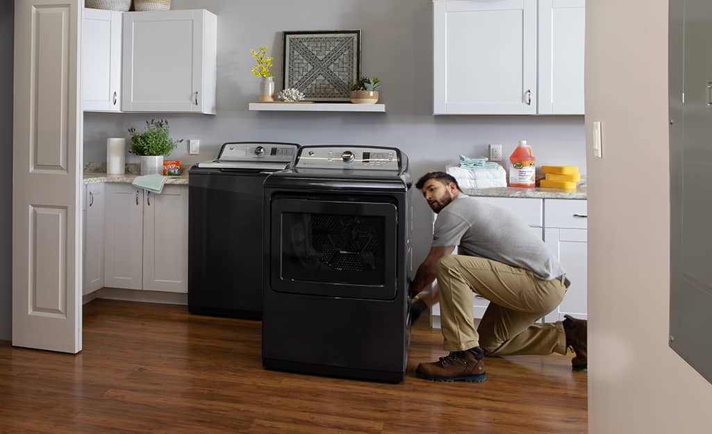 A man kneels down to install a new washing machine and dryer in a laundry room.