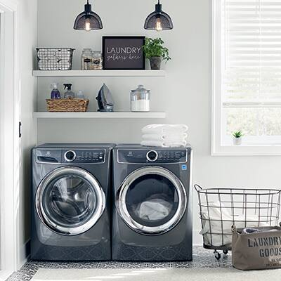A black washing machine and matching dryer in a laundry room beside a window.