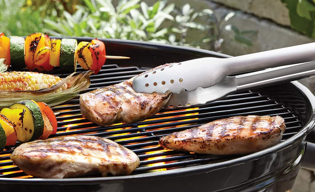 A person uses tongs to flip their grilled chicken.