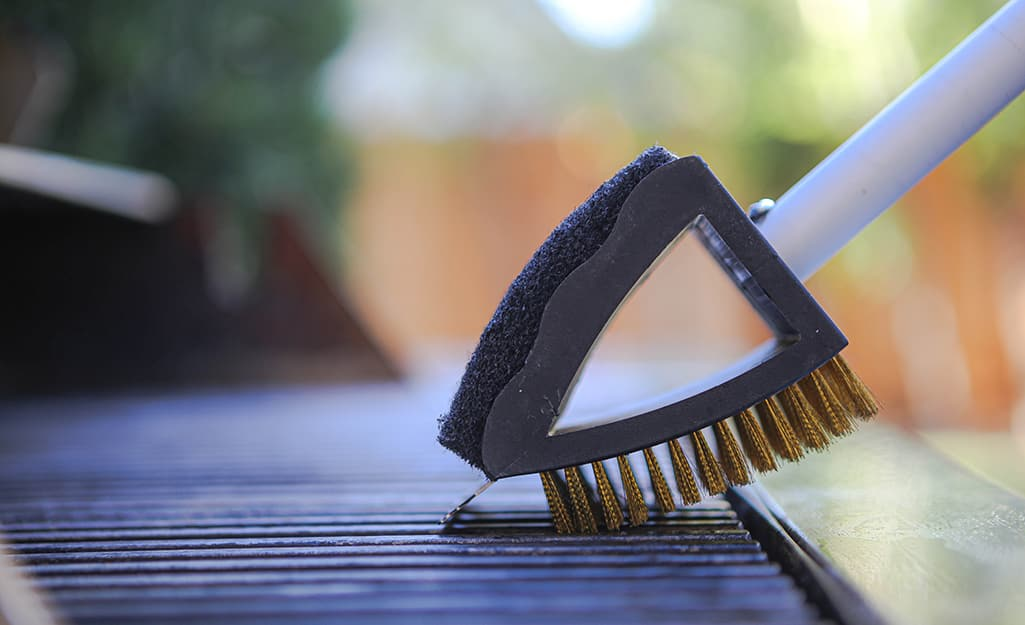 A grill brush is used to clean a grill grate.