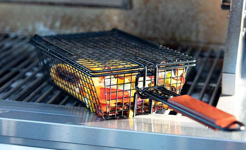 A long-handled grilling basket holds vegetables on a grill.