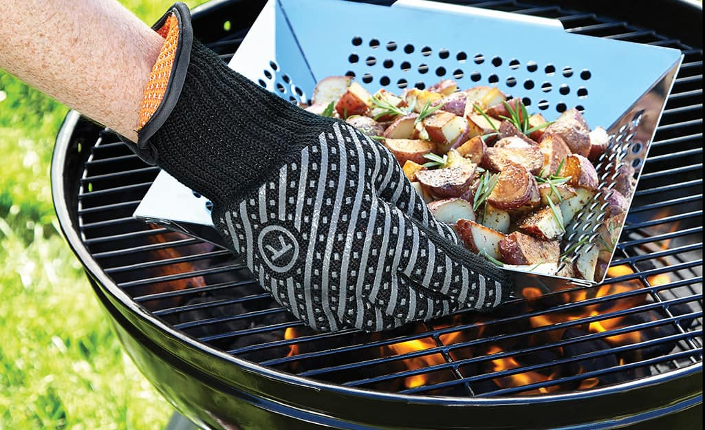 A person wears grilling gloves when using a charcoal grill.