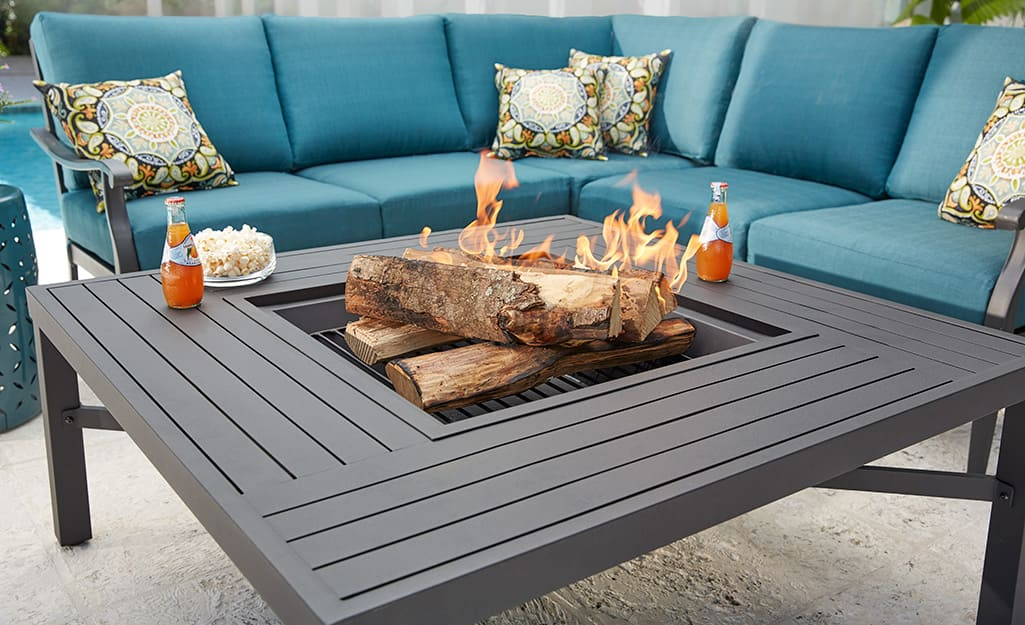 A Hampton Bay patio sofa set with blue cushions and a brown patio table with a built-in fire pit.