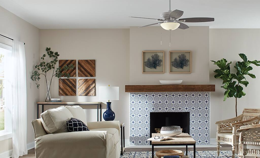 A living room with a white sofa, coffee table and a Hampton Bay ceiling fan.