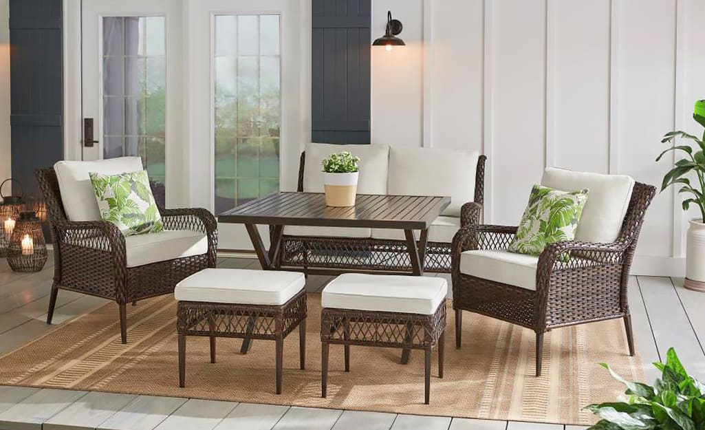 A Hampton Bay patio set in brown wicker with white cushions.