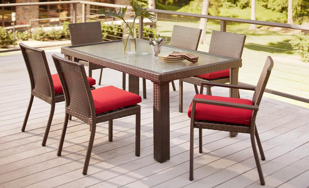 A Hampton Bay patio set with a table and six chairs with red cushions.