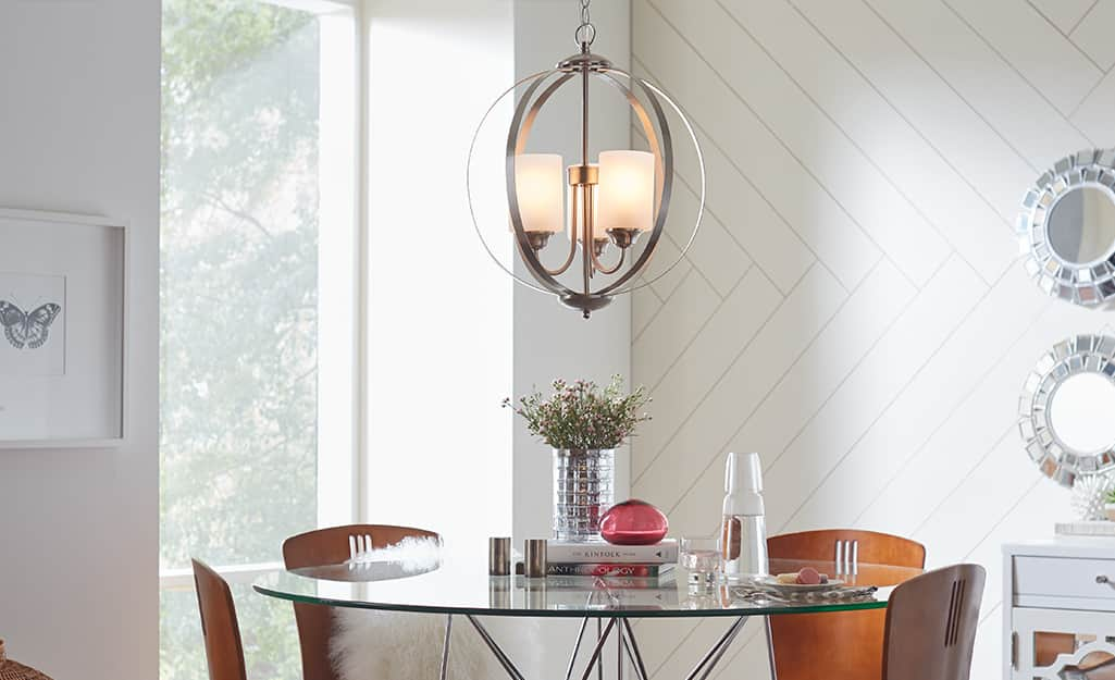 A Hampton Bay chandelier lighting fixture over a glass-topped table with chairs.