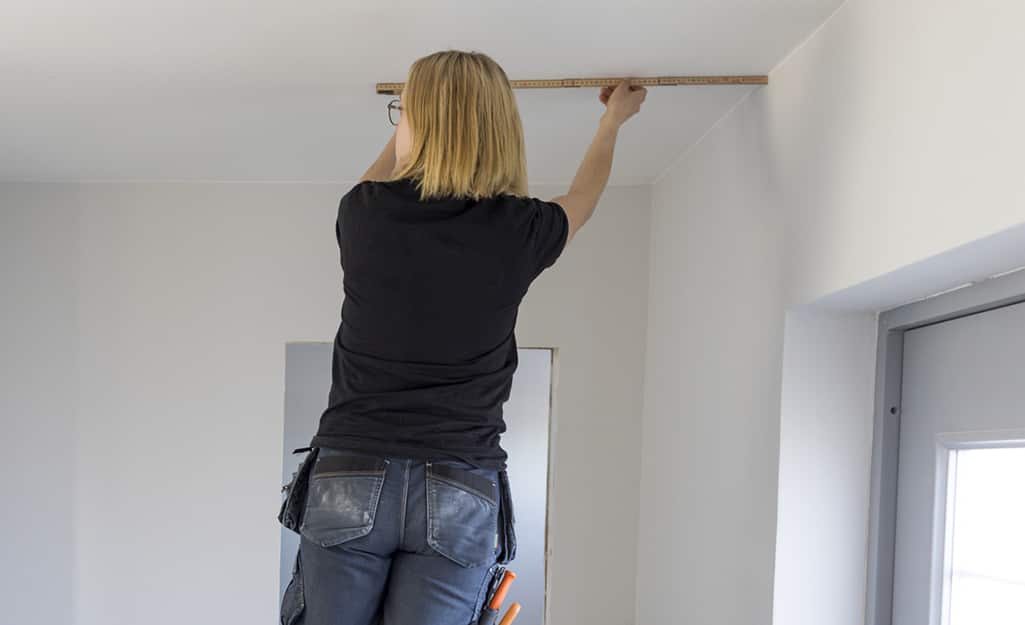 A person uses a ruler to make measurements on the ceiling.