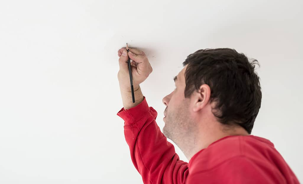 A person marks the spot to install a mounting bracket.