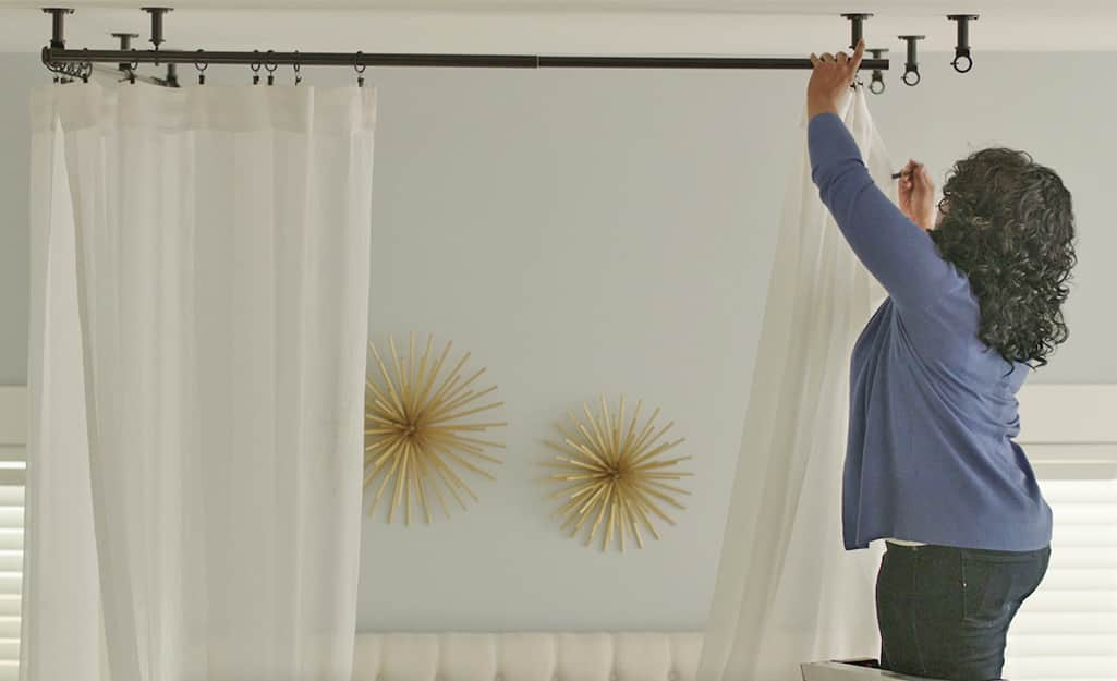 A person hangs draperies on a ceiling-mounted rod.