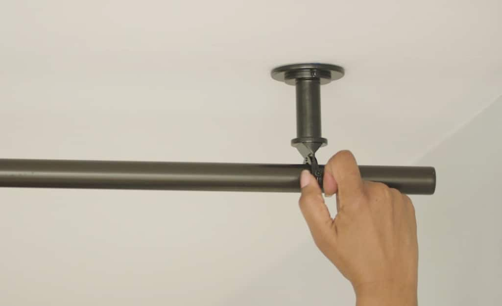 A person hangs a curtain rod on a ceiling-mounted hook.