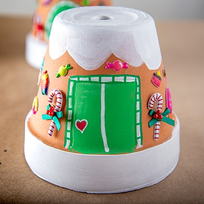 A terra cotta pot painted like a gingerbread house.