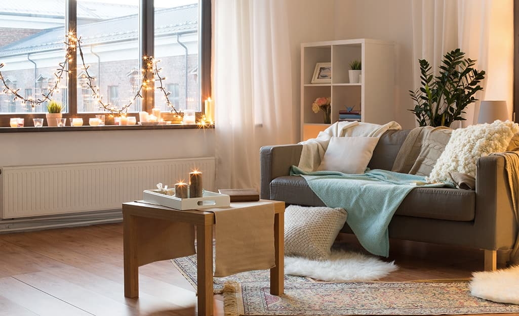 Holiday string lights and candles decorate a window sill and coffee table in a living room.